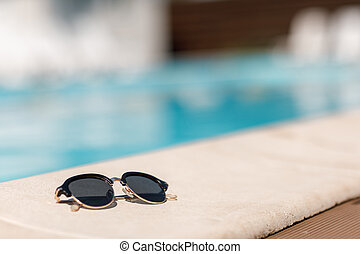 sunglasses by the pool on a sunny summer day.