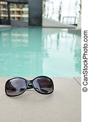 Sunglasses by the swimming pool