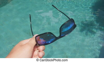 sunglasses fall into the pool and fall under the water -...