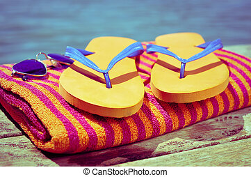 sunglasses, flip-flops and beach towel, on a wooden ...