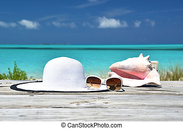 Sunglasses, hat and conch against ocean. Exuma, Bahamas