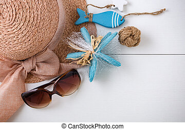 Sunglasses, hat and summer accessories on white wood background