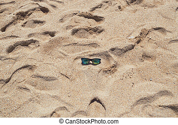 sunglasses in the center of shiny beach sand