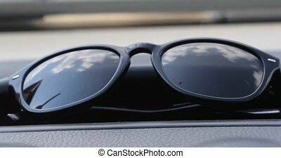 sunglasses in which the clouds are reflected.