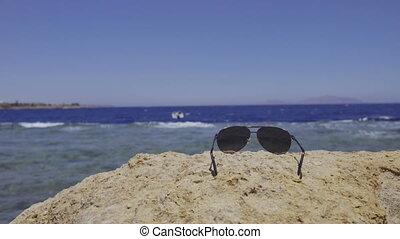 Sunglasses lying on stone on beach, focus on glasses