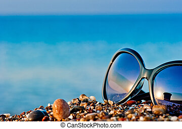 sunglasses lying on the beach on the wet pebbles