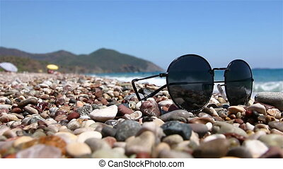 Sunglasses on a pebble beach by the