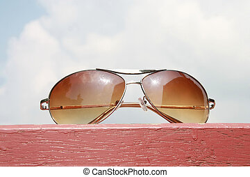 sunglasses on pink wood and cloudy sky background