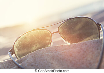 Sunglasses on sand at sunset, beach and ocean in the background.