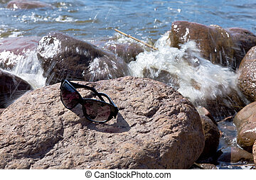 Sunglasses on stone by the sea