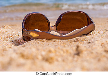 Sunglasses on the beach near the sea against the sea wave