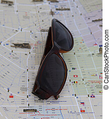 Sunglasses on the map. the concept of travel.