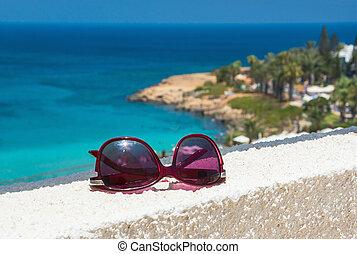 Sunglasses on the sea background