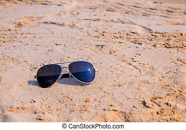 Sunglasses on the sea beach