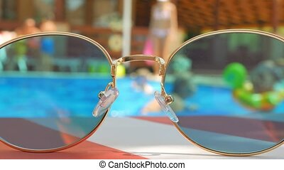 Sunglasses. Pool reflection. Concept of holiday at sea. Observations children, play.