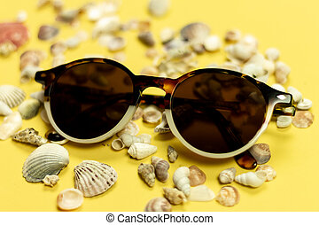 Sunglasses, shells and pebbles closeup on white background