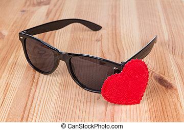 sunglasses wayfarer with heart symbol over wooden background