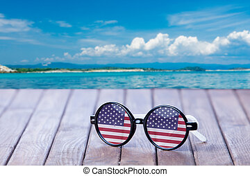 Sunglasses with american flag on wooden table