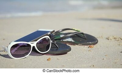 Sunglasses with beach slippers and mobile phone on the sandy...