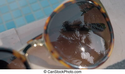 Sunglasses with palm reflection. Summer holidays - Close-up...