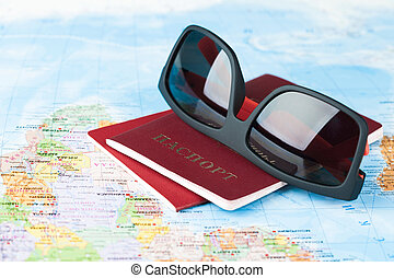 sunglasses with passports on the world map