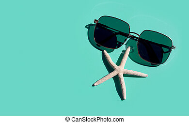sunglasses with starfish on blue background. Enjoy holiday concept.
