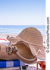 Sunhat and handbag on a sunny summer beach conceptual of a tropical vacation or travel
