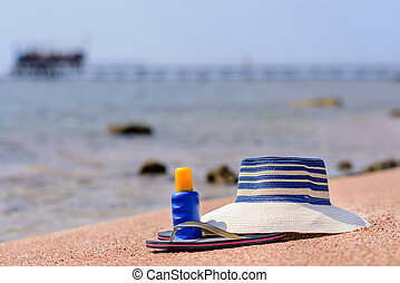 Sunhat, thongs and sunscreen on a beach