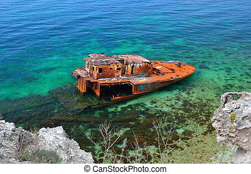 Sunk ship in blue water, aground, near the coast.