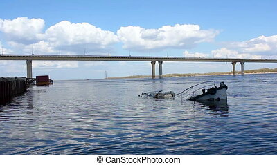 Sunken ship in the river - Bridge over the river and a...