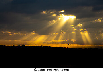 Sunlight beams in the clouds at sunset over the city