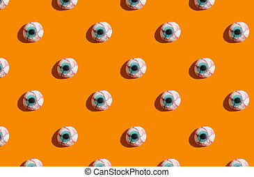 sunlight pattern made with marmalade in form of monster eyes on bright orange background.