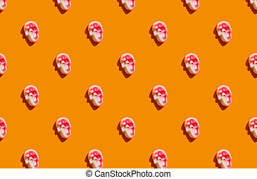 sunlight pattern made with marmalade in form of skull on bright orange background.