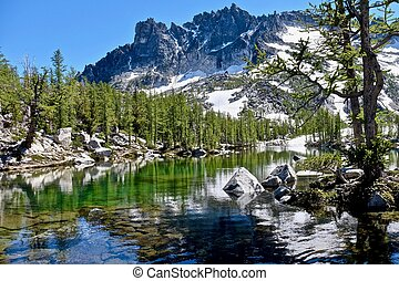 Sunlit alpine forest, clear lake and granite mountain. -...