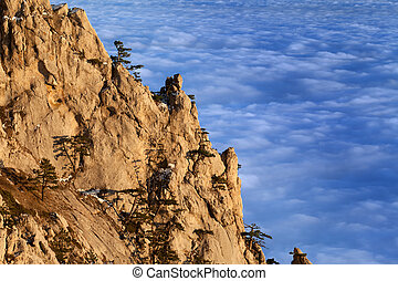 Sunlit cliffs and sea in clouds at evening