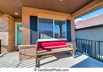 Sunlit open front porch of home with wooden bench against window with shutters