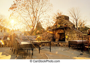 Sunlit Patio With Stone Fireplace - Low-angle view of a...