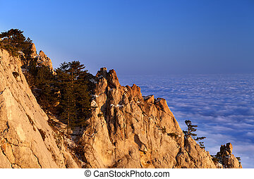 Sunlit rocks and sea in clouds at evening