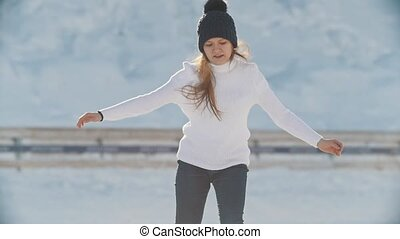 Sunlit teen girl skillfully skating on outdoor public ice...