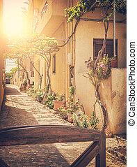 Image of a sunlit village street. Crete, Greece. Vintage styled.