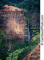 A sunlit waterfall on the island of Kauai.