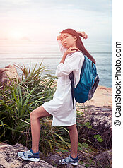 Sunny asian woman with backpack in white dress posing on stone near the sea