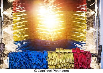 Sunny Automatic Car Wash. Spinning Colorful Brushes and the Sun in the Middle.