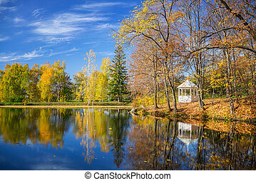 Sunny autumn landscape with blue sky over the lake