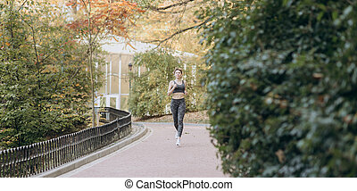 Young active female athlete exercising outdoor in the sunny autumn