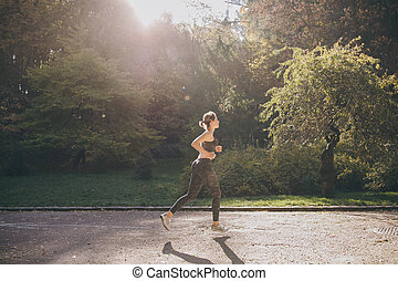 Young active female athlete exercising outdoor in the sunny autumn. Running close to a park.