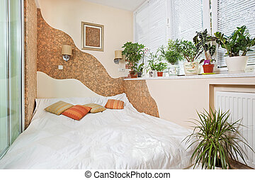 Sunny bedroom on balcony interior with Window and plants,...