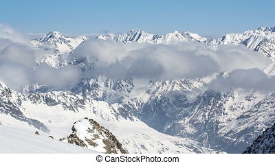 Sunny Day Above Low Clouds in Winter Snowy Alps Mountains...