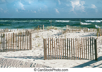 Beautiful landscape or seascape of white sand beaches, puffy clouds, cheerful sand fences and emerald tropical waves with frothy breakers on a sunny day at Pensacola, Florida beach.