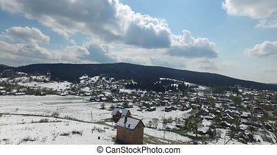 Sunny day on a small village on the hillside, green forest...